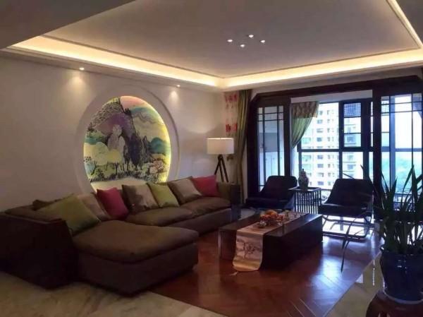 客厅区域,业之峰装饰公司设计师在设计客厅,硬装造型比较简洁,没有使用主灯,运用灯带、筒灯、射灯等光源营造灯光氛围,让空间时尚,主要运用咖啡色沙发、中式画、中式隔断等综合运用让家里有中国文化氛围。