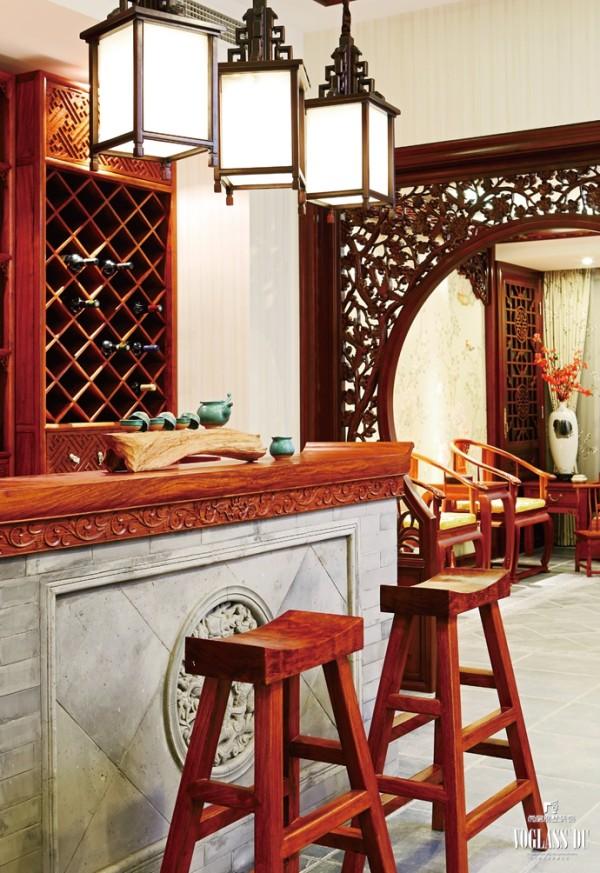酒吧的设计完全遵循中式风格,电梯一开门便看到青砖砌筑的吧台,一方茶具静置其上,恬淡、安静的家庭气质油然而生。花梨木雕筑的博古架上陈列了女主人各式各样的收藏品,精心安排的灯光让整个空间更有层次。