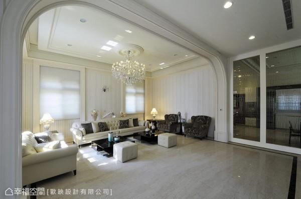 沙发区与电视墙前过道以一道大拱框划界,于家私摆设中,对称安定的古典语汇围塑贵气优雅姿态。
