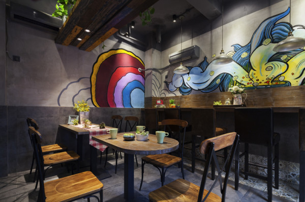 就餐区,空间整体以灰色调呈现,运用了做旧的地板加以彩色油漆,颜色跳跃的丙烯墙绘使整个空间显得格外活泼起来。