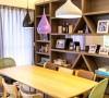书房区以木作设计的桌椅与整面展示柜为主,不同色彩的灯饰高低坐落,注入活泼生动的气息。