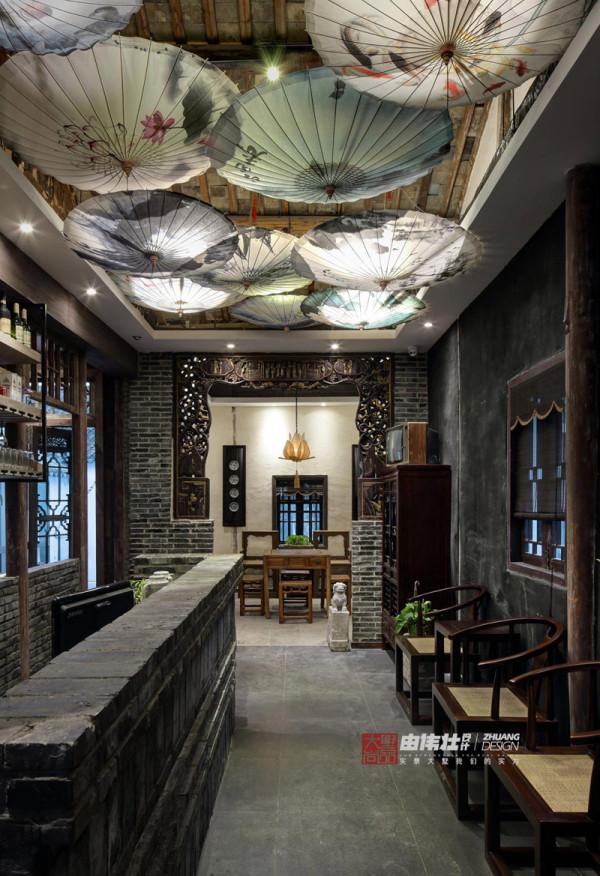 进门后左侧的吧台区域利用小青砖堆砌,简单地刷制清漆,搭配顶上的油纸伞、远处的老花格,让整个吧台区域意境满满。
