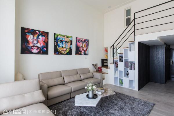 在梯下设计虚实相间的展示柜体,艺术画作装饰沙发墙,简洁之中展现美学色彩。