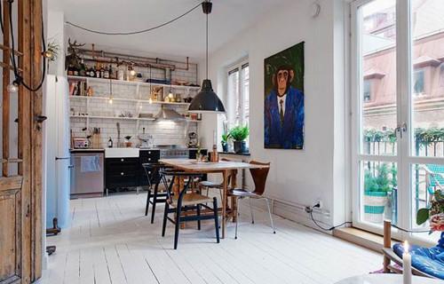 餐厅被房主设置在厨房空间之中,木色餐桌在整个浅色系空间中显得自然,顶部的黑色简约吊灯能够给到这一区域适度的照明,在用餐区一旁的墙面上以一幅动物形象的装饰画来装饰墙面,让这个空间中显现出活跃有趣的氛围。