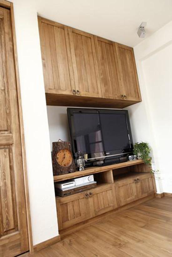 木质的地板搭配木质的家具,整体非常协调。悬空式的收纳柜,非常节省空间。电视柜的下方,可以放上遥控器,CD等,方便主人拿取。