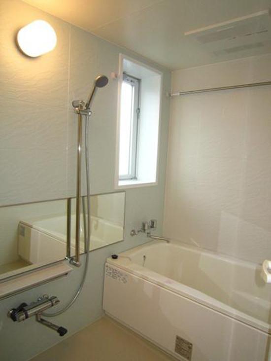 淡绿色的墙壁搭配黄色的地板,清新怡人,令人身心放松。白色的大浴缸,舒适之感一涌而出。白色圆柱状壁灯,简单大方。