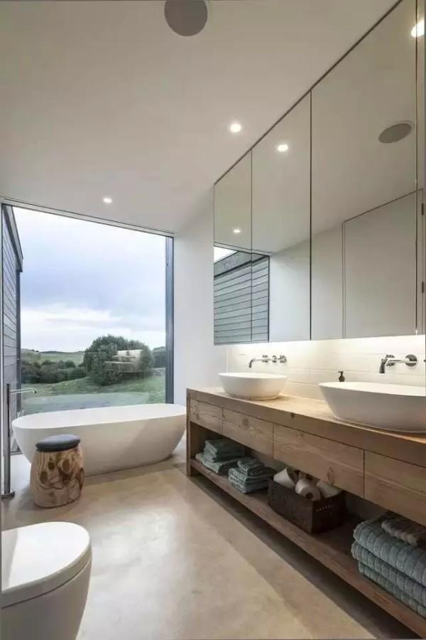 光滑墙面点缀下的开放式卫浴设计。大的落地窗,外面是开阔的风景一线,白色的卫浴空间,大大的浴缸是最舒适的角落。