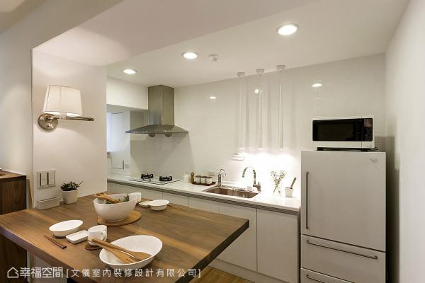 利用柜体深度规划的餐桌为活动式设计,而开放式厨房也采白色调与造型光影投射,融入整体设计语汇中。