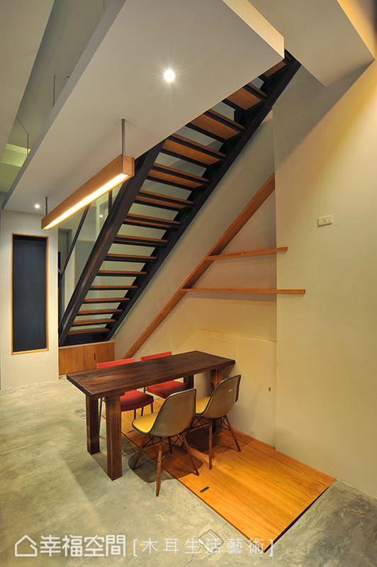 善用楼梯下方空间为会议区,天花以长形造型及吊灯勾勒出独立场域,地上的木片掀起来可以通往地下室。