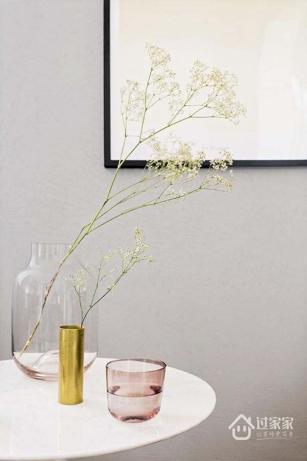 在角落上的设计都以极简优雅的理念为主,无论是通往房间的过道,还是通往淋浴室的那抹蓝抢以及桌上清新感十足的小花。