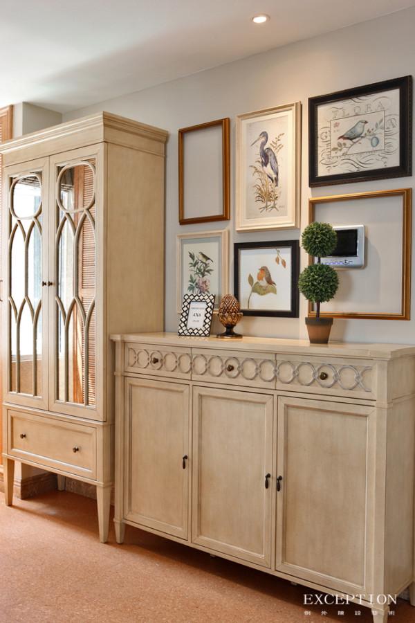 玄关特写,撤去占满整面墙壁的白色储物柜,高低组合的仿古衣鞋收纳柜,外观雅致,组合挂画巧妙的将可视对讲机弱化,和谐而富有创意。