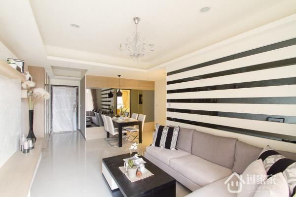 考量到客厅公领域的幅度较小问题,设计师不仅减少了收纳柜体比例更以立体黑镜线条勾勒背墙,进一步放大出公领域视野。