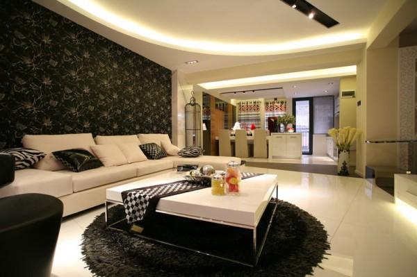客厅装修:黑白色的经典搭配,白色的空间以及白色的沙发,发配黑色的靠包,以及黑色的背景墙,有效的衔接,使空间看起来充满现代都市生活的时尚感