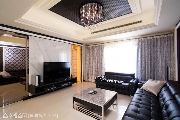 为烘托电视墙器度,戴世慧设计师在两侧安排大面茶镜喷砂,拉阔视觉尺度,同时隐藏通往餐厨区门片。