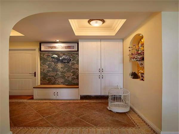 进门玄关处的衣帽柜、换鞋凳一体设计,地面用仿古砖走边拼花铺贴。