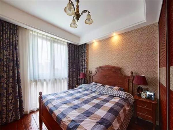 次卧父母房间用了比较传统的实木床,同样色系的衣柜移门。