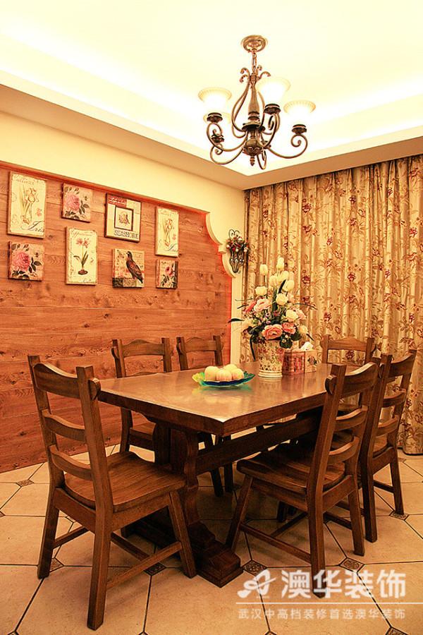 原木材质的餐桌颇具古典味道,满足了业主与朋友偶尔小聚的生活需求。铁艺灯和木饰面板是美式乡村风格的标志,配上几幅花鸟工艺装饰画,让人在就餐时轻松享受墙壁上的风景。