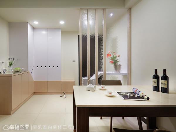 后方鞋柜以双色与斜线造型作为柜体呈现,温润质感持续延伸到室内的餐桌区,共享温馨氛围。