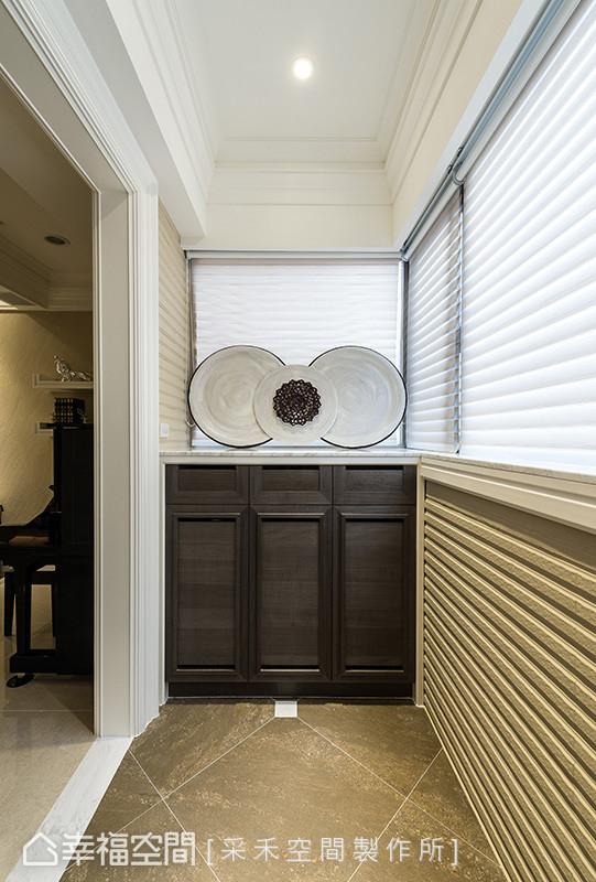 地坪以金属感的半抛石英砖作为铺陈,鞋柜上方以圆弧形的视觉堆栈,创造一处艺术端景。