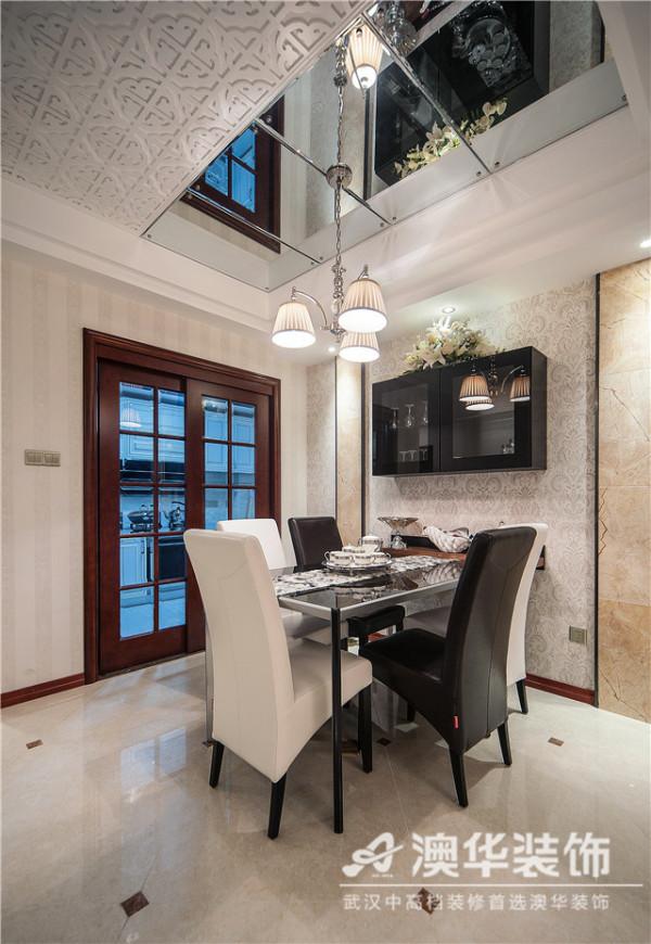 整体布景与客厅保持一致性,在功能分区上并无实墙或隔断,仅以石膏拼花图案和透明玻璃饰块做装饰,同样温馨雅致又别具一格的设计成为视觉中心。经典黑白配餐台,摆放精致餐碟,凸显主人追求优质质感的生活品位。