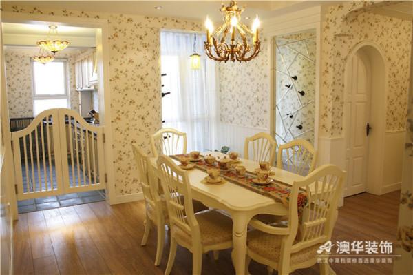 餐厅设计在田园味道的主基调上,增添了地中海式的纯净与澄澈。厨房与餐厅之间以一扇栅栏隔开,临近白色缥纱的墙面设计成木桩造型,实用而富有创意。白影木材制成的餐桌上,浓郁的法式器皿与铁艺烛台相映成趣。