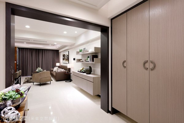 除了设置大面积鞋柜创造收纳机能之外,采舍空间设计也透过门框设计界定出玄关空间。