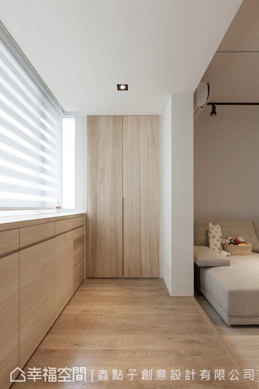 虫点子设计架高入口区的地坪,藉此来区分与客厅的机能;端景柜的设计,则能放置外出衣物与伞具等。