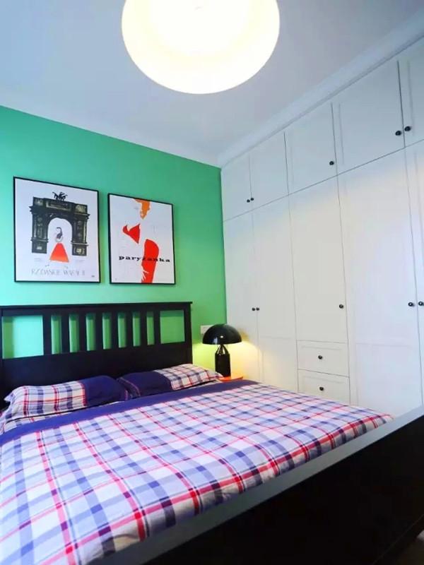主卧卧室一面墙做了大衣柜,采用绿色墙面做床头,红与黑搭配的床和床头柜。