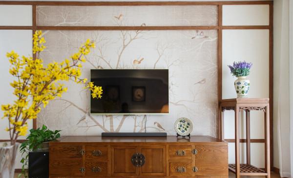 设计师在沙发背景有序的重复了端景的造型,梅花点状的壁纸和小鸟装饰从色彩和主题上都呼应了电视背景。米色坐垫的中式沙发搭配水墨画的靠垫契合了业主追求的沉稳内敛的气质。