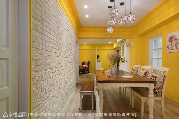 延续暖黄色调的餐厅另筑一面文化石墙,定义视觉重心并增添质朴表情。