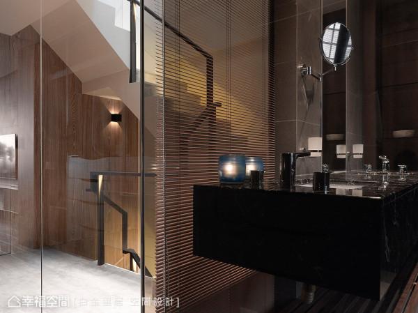 从梯间、更衣区一路进入卫浴空间,都充满了精品饭店式的质感与氛围;梯间延续到主卧的立面,则是以双染色木皮来铺陈。