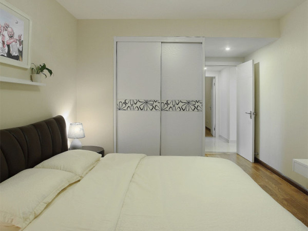 整个卧室都是十分简洁淡雅,衣柜起到分隔空间的作用。
