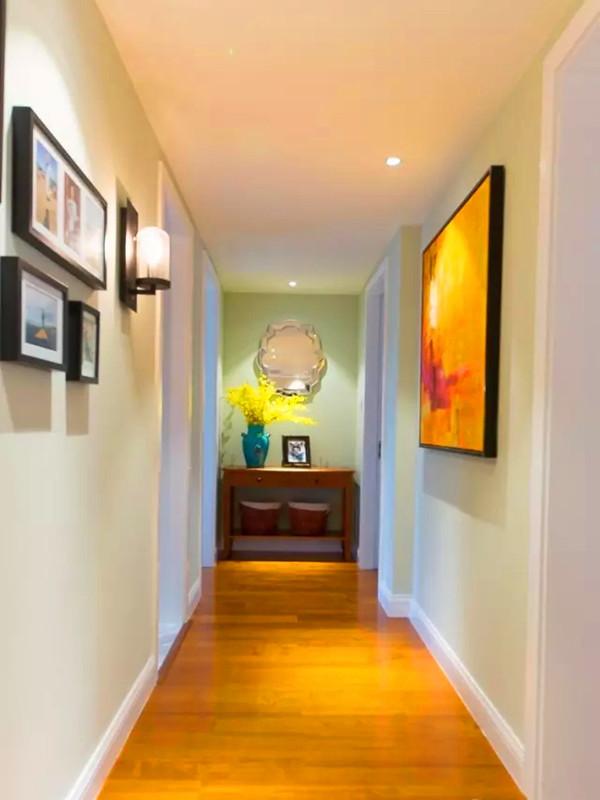 走廊延续淡绿色,两边用照片墙和油画装饰。