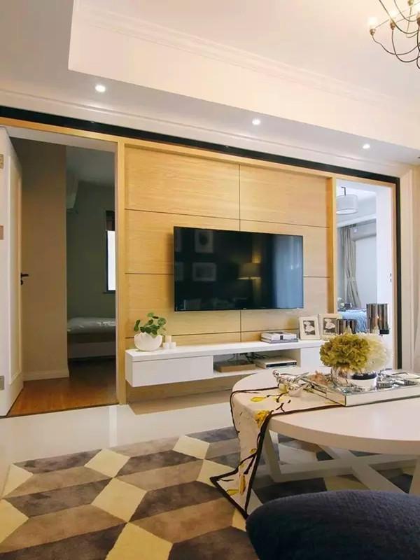 电视背景左右分别是主卧和书房的门,以白色漆、黑镜、木材搭配,让电视背景造型符合对称美学。
