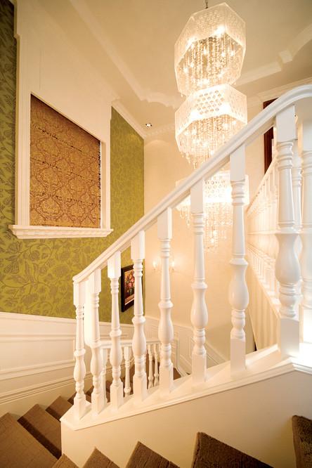 象牙白的楼梯扶手和水晶吊灯,整体的墙面顶面都已暖色为主导。