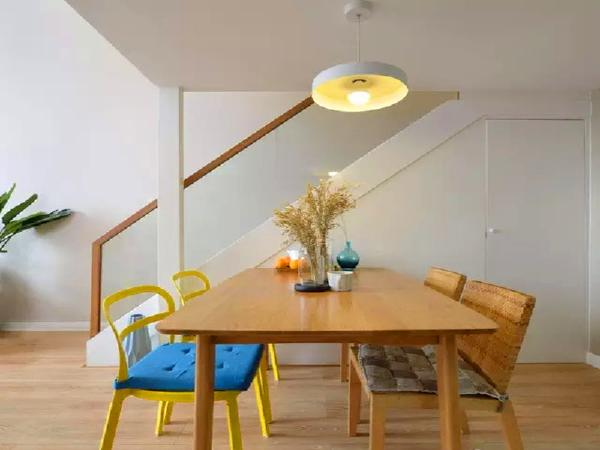 实木的餐桌,混搭两张黄色的金属椅和两张藤椅。