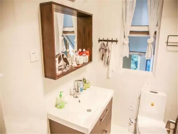 卫生间整洁明亮。在镜子外面镶上一圈方格的厚实木框,还能把洗漱用品放在木框上,风格简单,却也实用。