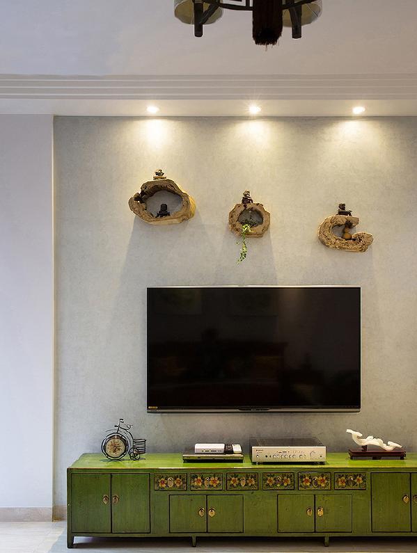 菠菜绿电视柜给人以清新的感受和自然韵味让人印象深刻。仿丝绒的艺术涂料电视背景墙,带给人丝丝质感,用树墩作墙壁装饰再加上几个小和尚做摆件,成为居室里一道独特的缀饰。
