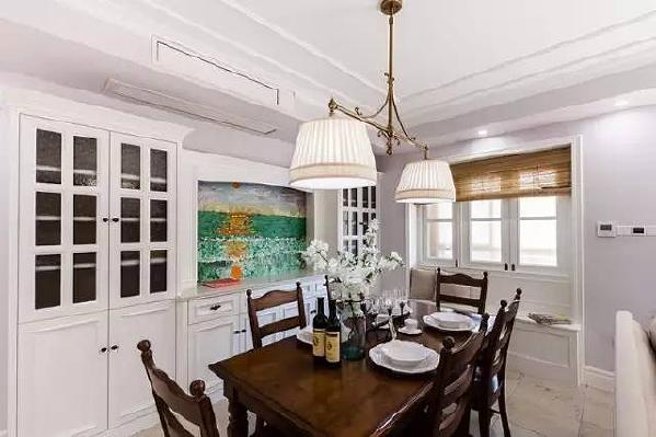 另一面的墙壁打造了整面墙的餐边柜,白色的柜体仿佛与墙面融为一体,透明的  玻璃门方便主人随时欣赏到喜欢的装饰物和餐具。