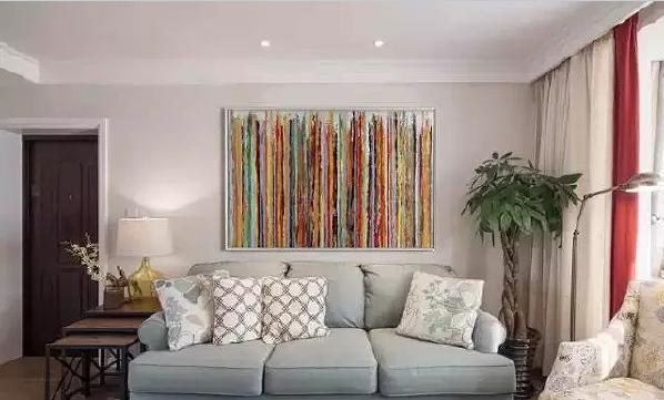 """沙发墙是家里最""""色""""的地方,个性的彩色条纹挂画让客厅充满色彩和活力,浅  色的家具仿佛都成了陪衬。"""