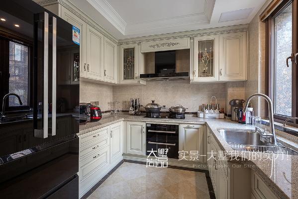 厨房是一个敞开的U型厨房,双开门冰箱可以储备很多食材。宽敞的台面足够女主人为家人做出各种丰盛的食物。仿古的墙砖地砖让厨房更加温馨起来。
