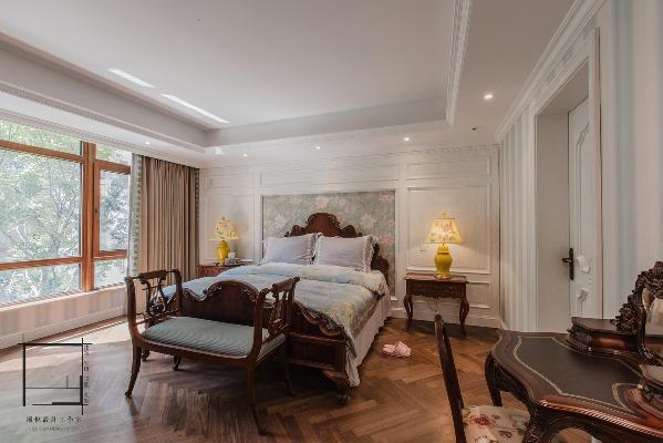 白天的主臥室光線明媚,墻面壁紙與墻板顯得清新,地面人字拼花又不失古典風格的傳承,最後配上美式家具的穩重。
