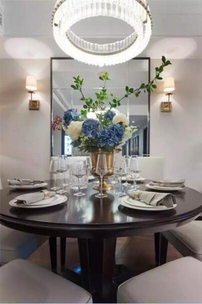 圆形吊灯与圆形的餐桌对应,好似团圆的寓意。一面大大的镜子让餐厅显得更明亮,深色的木桌也显得毫不暗淡。