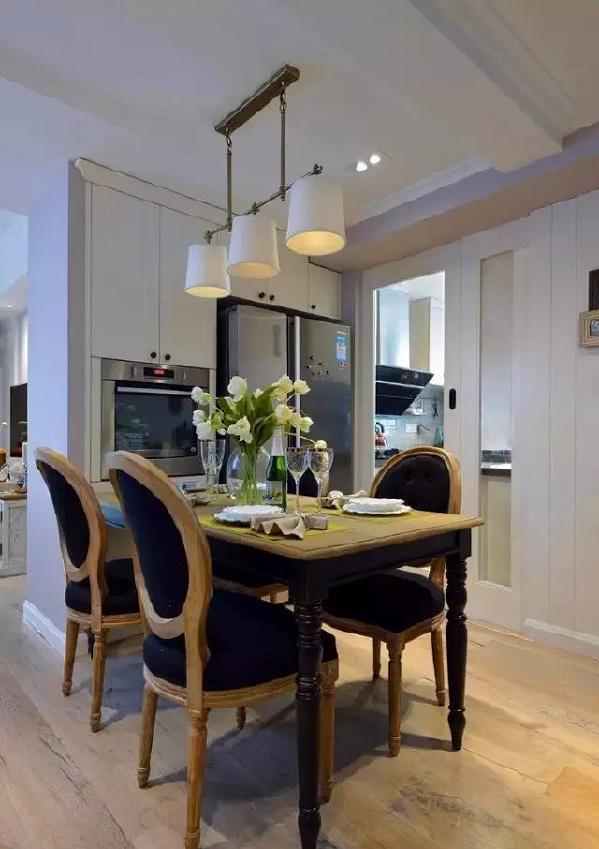 ▲ 和客厅的隔墙设计成组合柜体,融入冰箱和嵌入式厨房电器