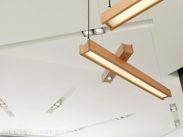 谭淑静设计师亲自设计的造型灯具,延续自天花板的灯槽语汇,温润的木质外型搭配柔美光氛,成为空间中一道视觉亮点。