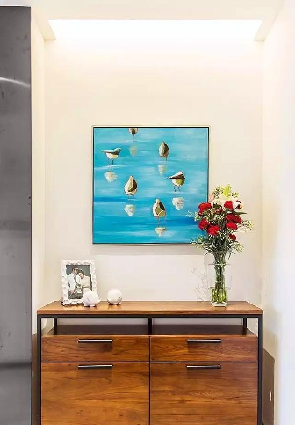 ▲ 进门的玄关柜子,实木和铁艺搭配出复古的质感,一幅清新的蓝色装饰画