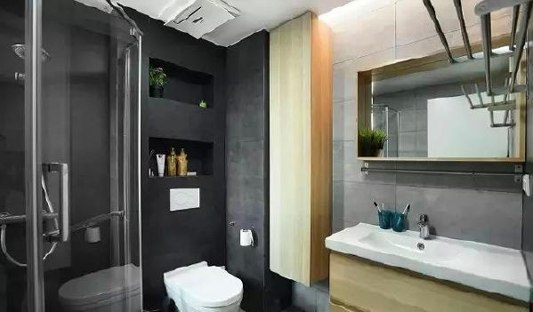 ▲ 黑色和灰色双拼砖,利用壁挂式马桶的墙壁空间做内嵌柜,木色大吊柜实用又漂亮