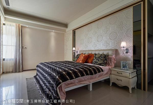 灰镜佐木框的床头主墙贴饰珠光壁纸,有别于公共空间的刚硬利落,表现主卧房的柔软与华美气质。