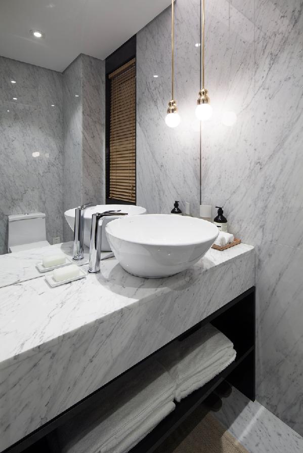 卫生间沿用了客餐厅的大面石材,使空间更为统一。淋浴间和马桶间分为两个空间。为了提高空间利用率,淋浴间的门设计成石材暗门,从外面看与玄关区域融为一体,美观又实用。