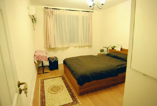 另一个房间相对来说很明亮,也是做了很简洁的设计,没有其他多余的装饰,实木床和实木的地板很好的彰显了主人的品味。